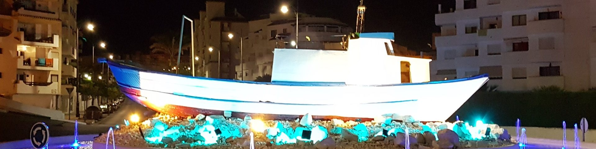 Roundabout at the entrance to Estepona Port with a boat in the centre